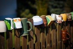 Кружки и баки вися на загородке Стоковое Фото