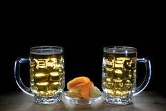 2 кружки пива и картофельной стружки против черной предпосылки Стоковые Фотографии RF