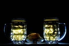 2 кружки пива и картофельной стружки против черной предпосылки Стоковая Фотография RF
