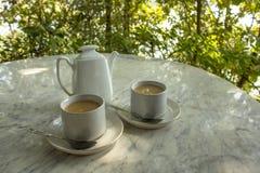 2 кружки с напитком молока на плитах с ложками около белого керамического чайника на мраморной таблице на запачканной предпосылке стоковое изображение