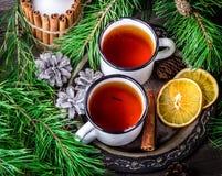 2 кружки чая на винтажном подносе металла и свече, ветвях сосны на деревянной предпосылке Стоковое фото RF