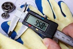 Крумциркуль цифров и работая перчатки на таблице с техническими чертежами Стоковые Изображения