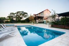 Крупный план бассейна рядом с садом дома стульев современным стоковое фото rf