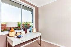 Крупный план белой таблицы с книгами и орнаментальными деталями изолированными около стеклянного окна в современной комнате стоковые фото