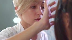 Крупный план белокурого женского визажиста прикладывая косметики с пальцами на стороне женщины брюнета сток-видео