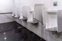 Крупный план 3 белых писсуаров в ванной комнате людей, дизайне белых керамических писсуаров Стоковые Фото