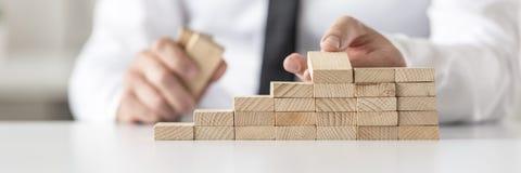 Крупный план бизнесмена аранжируя деревянные колышки в лестницу Стоковое Изображение RF