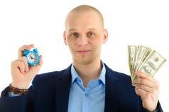 Крупный план бизнесмена с будильником и стог денежных средств в кассе Время принципиальная схема дег Стоковая Фотография