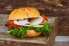 Крупный план бургера сыра домашних сделанных бургеров говядины с салатом служил на маленькой деревянной разделочной доске Стоковые Фото