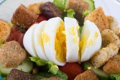 Крупный план вареного яйца которое плохо было отрезано na górze салата стоковое изображение