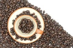 Крупный план взгляд сверху кофейной чашки заполнил с зажаренными в духовке кофейными зернами o зажаренных в духовке кофейных зере Стоковое Фото