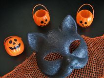 Крупный план взгляд сверху маски кота хеллоуина потехи и смеясь над мини Джек-o-фонарики на черном фоне Стоковые Фотографии RF