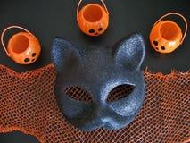 Крупный план взгляд сверху маски кота хеллоуина потехи и усмехаясь мини Джек-o-фонарики на черном и оранжевом фоне Стоковое Фото