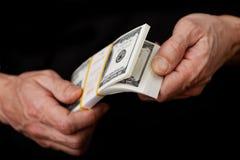 Крупный план вручает переучитывать банкноты в пачке долларов Стоковая Фотография RF