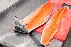 Крупный план высекая все свежие норвежские рыб семг с ножом на красной стоковое изображение rf