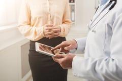 Крупный план доктора указывая в таблетку и пациента стоковые изображения