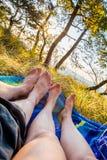 Крупный план женских и мужских ног лежа на одеяле на заходе солнца Стоковые Фотографии RF