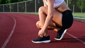 Крупный план женского бегуна связывая шнурки на тапках акции видеоматериалы