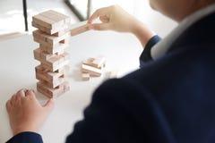 Крупный план женщин играя игру стога деревянных блоков, концепцию роста дела, glambling, риск стоковое изображение rf
