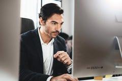 Крупный план жизнерадостного бизнесмена работая на офисе просторной квартиры Человек используя современный настольный компьютер г Стоковые Фото