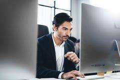 Крупный план жизнерадостного бизнесмена работая на офисе просторной квартиры Человек используя современный настольный компьютер г Стоковое Изображение RF