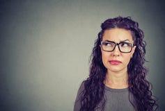 Крупный план заботливой молодой женщины в стеклах смотря вверх предусматривающ стоковая фотография