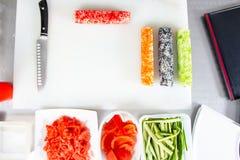 Крупный план завальцовки вверх по сушам на кухне с ножом и ингредиентами стоковые фото