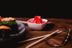 Крупный план замариновал имбирь, ручки, Wasabi и соевый соус для суш на коричневой предпосылке деревянного стола Взгляд сверху Стоковая Фотография