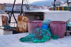 Крупный план зеленой рыболовной сети, ржавой цепи и vats перед шлюпкой стоковые изображения rf