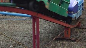 Крупный план колеса старой уменьшительной американской горкы проходит дальше рельс в парке атракционов Люди в будочках едут внутр акции видеоматериалы