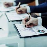 Крупный план команды дела работает с финансовыми план-графиками в рабочем месте в офисе Стоковые Изображения