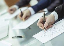 Крупный план команды дела работает с финансовыми план-графиками в рабочем месте в офисе Стоковые Изображения RF