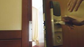 Крупный план коммерсантки в двери гостиничного номера костюма открытой используя безконтактную ключевую карточку и вход комнаты П видеоматериал