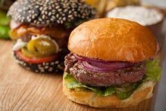 Крупный план комплекта мини домодельного бургера 3 с мраморными говядиной и овощами на деревянной доске Стоковая Фотография