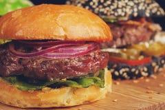 Крупный план комплекта мини домодельного бургера 3 с мраморными говядиной и овощами на деревянной доске Стоковое фото RF