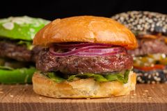 Крупный план комплекта мини домодельного бургера 3 с мраморными говядиной и овощами на деревянной доске Стоковая Фотография RF
