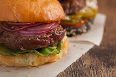 Крупный план комплекта мини домодельного бургера 3 с мраморными говядиной и овощами на деревянной доске Стоковое Изображение RF