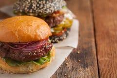Крупный план комплекта мини домодельного бургера 3 с мраморными говядиной и овощами на деревянной доске Стоковые Изображения