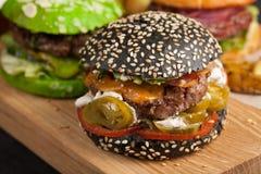 Крупный план комплекта мини домодельного бургера 3 с мраморными говядиной и овощами на деревянной доске Стоковые Фото