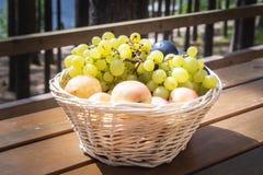 Крупный план корзины с виноградинами, персиками и выступать на деревянном столе, внешней партии или пикнике стоковое фото