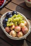 Крупный план корзины с виноградинами, персиками и выступать на деревянном столе, внешней партии или пикнике, взгляд сверху стоковое изображение rf