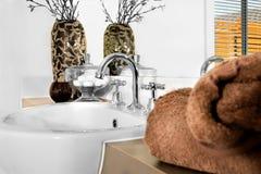 Крупный план коричневого полотенца цвета и фокусируя современного белого умывальника с faucet в роскошных доме или гостинице стоковая фотография rf