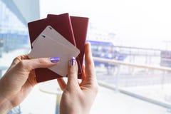 Крупный план красивой руки женщины держа пасспорты и билеты посадочного талона на крупном аэропорте Концепция перемещения и празд стоковое фото