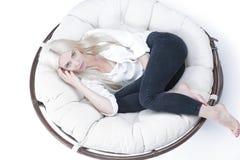 Крупный план красивой унылой молодой женщины сидя в большом comfor стоковые фотографии rf