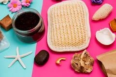 Крупный план красочных объектов спа и заботы, небольших цветков, scrub, washcloth и seashells на пинке и голубое стоковое фото