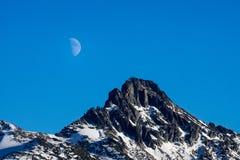 Крупный план луны поднимая над горным пиком стоковое фото rf