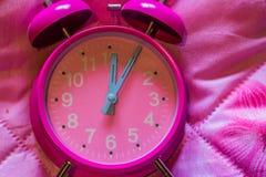Крупный план макроса розового винтажного будильника на розовой предпосылке стоковые изображения rf