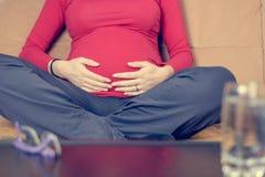 Крупный план матери вручает ласкать ее беременный живот стоковая фотография