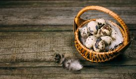 Крупный план меньшая корзина с яичками триперсток около стойки пера на деревенской деревянной предпосылке Насмешка пасхи или охот Стоковые Фотографии RF