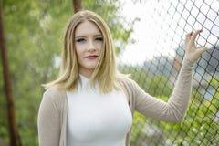 Крупный план милой молодой женщины стоя близко загородка звена цепи стоковое изображение rf